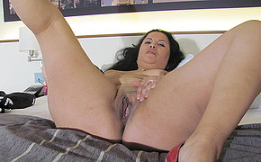 Kinky mature slut playing on her bed all round a dildo