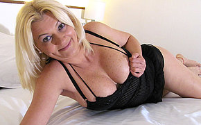 Blonde mature slut playing with herself on the top of the bed